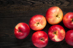 Some red apples on the table. Some red apples on the dark wooden table Royalty Free Stock Photo