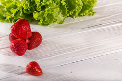 Some red berries of strawberry and lettuce leaves on white board. S. Close up, horizontal shot Stock Image