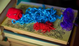 Some red, blue and purple antique ropes on a stack of old books. Some red, blue and purple antique ropes laying on a stack of old books Royalty Free Stock Images