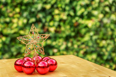Some red christmas balls with a big star in the center. On a wooden table Stock Photos