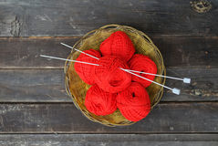 Some red clews in a basket. Red clews with needles in a basket on grey planks stock images