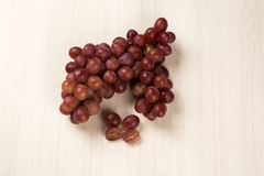 Some red grapes over a white background Stock Images