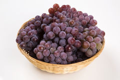 Some red grapes in a wooden pot over a white background Royalty Free Stock Photography