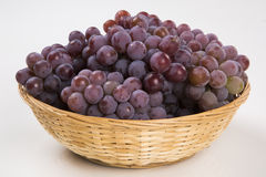Some red grapes in a wooden pot over a white background Stock Photography