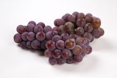 Some red grapes in a wooden pot over a white background Royalty Free Stock Photo