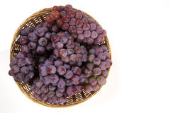 Some red grapes in a wooden pot over a white background Royalty Free Stock Photos