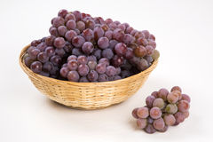 Some red grapes in a wooden pot over a white background Stock Image
