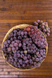 Some red grapes in a wooden pot over a wooden surface. Some red grapes in a wooden pot over a wooden surface seen from above Royalty Free Stock Image