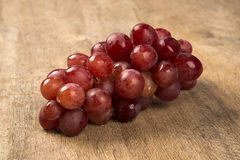 Some red grapes in a wooden pot over a wooden surface. Seen from above Royalty Free Stock Photography