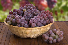 Some red grapes in a wooden pot over a wooden surface. Some red grapes in a wooden pot over a wooden surface seen from above Stock Image