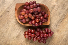 Some red grapes in a wooden pot over a wooden surface. Seen from above Royalty Free Stock Photos
