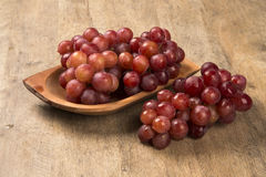Some red grapes in a wooden pot over a wooden surface. Seen from above Stock Images