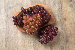 Some red grapes in a wooden pot over a wooden surface. Seen from above Stock Photography