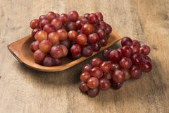 Some red grapes in a wooden pot over a wooden surface. Seen from above Royalty Free Stock Image