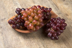 Some red grapes in a wooden pot over a wooden surface. Seen from above Royalty Free Stock Images