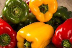 Some red, green and yellow peppers over a wooden surface. Fresh vegetable royalty free stock photography