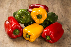 Some red, green and yellow peppers over a wooden surface. Fresh vegetable Royalty Free Stock Photo