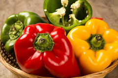 Some red, green and yellow peppers over a wooden surface. Fresh vegetable stock photography