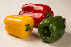 Some red, green and yellow peppers over a wooden surface. Fresh vegetable Royalty Free Stock Image
