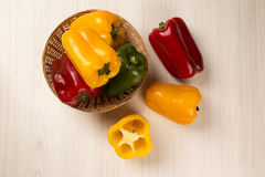 Some red, green and yellow peppers over a wooden surface. Fresh vegetable Stock Photos