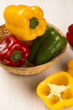 Some red, green and yellow peppers over a wooden surface. Fresh vegetable Stock Images