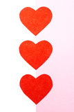 Some red hearts. Three hearts on the white-pink background Stock Photo