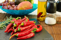 Some red hot chili peppers on a slate tray. With fruit and other ingredients on the background Stock Photo