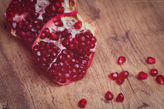 Some red juicy pomegranate. On dark rustic wooden table. Toned royalty free stock image