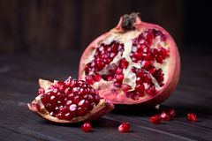 Some red juicy pomegranate. Whole and broken, on dark rustic wooden table stock image