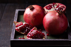 Some red juicy pomegranate. Whole and broken, on dark rustic wooden table royalty free stock photos