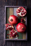 Some red juicy pomegranate. Whole and broken, on dark rustic wooden table royalty free stock photo