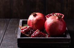Some red juicy pomegranate. Whole and broken, on dark rustic wooden table stock photos