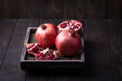 Some red juicy pomegranate. Whole and broken, in dark rustic wooden tray royalty free stock images