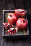 Some red juicy pomegranate. Whole and broken, in dark rustic wooden tray royalty free stock image