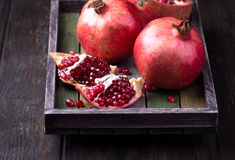 Some red juicy pomegranate. Whole and broken, in dark rustic wooden tray stock photography