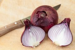 Red onions cutting with a knife on a wooden board. Some red onions cutting with a knife on a wooden board stock photography