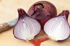 Some red onions cutting with a knife on a wooden board. Red onions cutting with a knife on a wooden board stock image