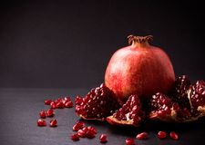 Some red pomegranates on black slate plate. Some red juicy pomegranate, whole and broken, on black slate plate Royalty Free Stock Images