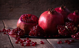 Some red pomegranates on old wooden table. Some red juicy pomegranate on dark rustic wooden table Royalty Free Stock Images