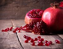Some red pomegranates on old wooden table. Some red juicy pomegranate on dark rustic wooden table Royalty Free Stock Image