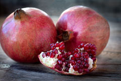 Some red pomegranates on old wooden table Royalty Free Stock Images