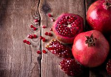 Some red pomegranates on old wooden table. Some red juicy pomegranate, whole and broken, on dark rustic wooden table Stock Photography