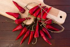 Some red spicy chili peppers. On wooden table royalty free stock image