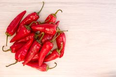 Some red spicy chili peppers. On wooden table royalty free stock photo