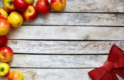 Some red and yellow apples on the white wooden table. Some red and yellow apples and Festive red bow on the white wooden table. food and dietary concept. picture Stock Images