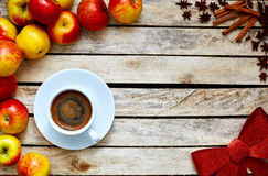 Some red and yellow apples on the white wooden table. Some red and yellow apples, Festive red bow, kitchen herbs and cup of coffee on the white wooden table Stock Photo