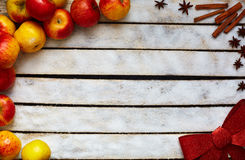 Some red and yellow apples on the white wooden table. Some red and yellow apples, Festive red bow, sugar, kitchen herbs on the white wooden table. food and Stock Images