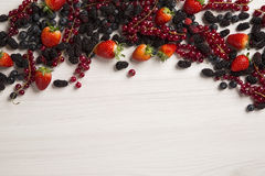 Some Redfruits over a wooden table. Some gooseberries, raspberries, strawberries and blueberries over a wooden table Royalty Free Stock Images