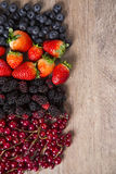 Some Redfruits over a wooden table. Some gooseberries, raspberries, strawberries and blueberries over a wooden table royalty free stock photography