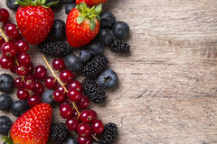 Some Redfruits over a wooden table. Some gooseberries, raspberries, strawberries and blueberries over a wooden table stock image